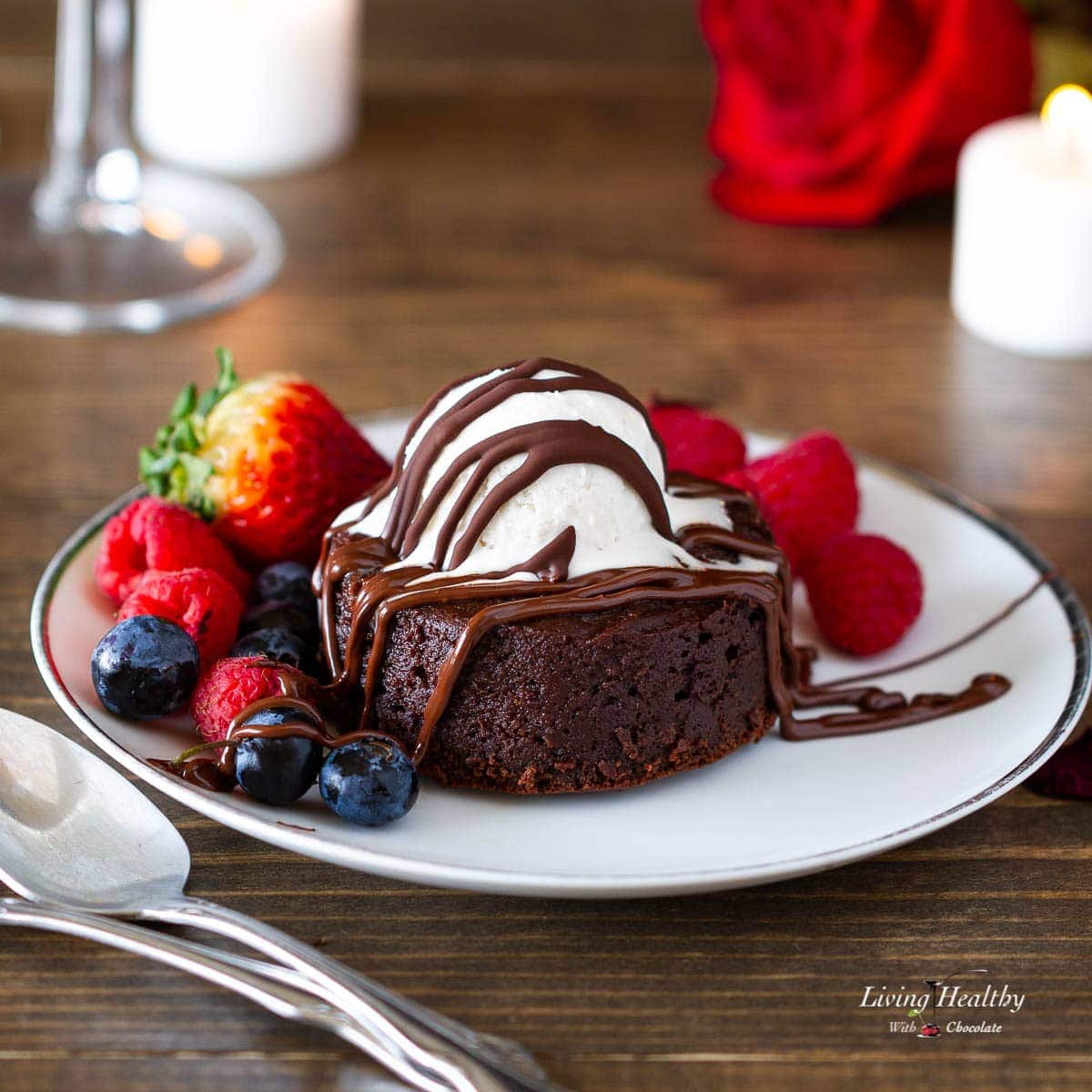 molten lava brownie with whipped cream berries and chocolate sauce on a plate