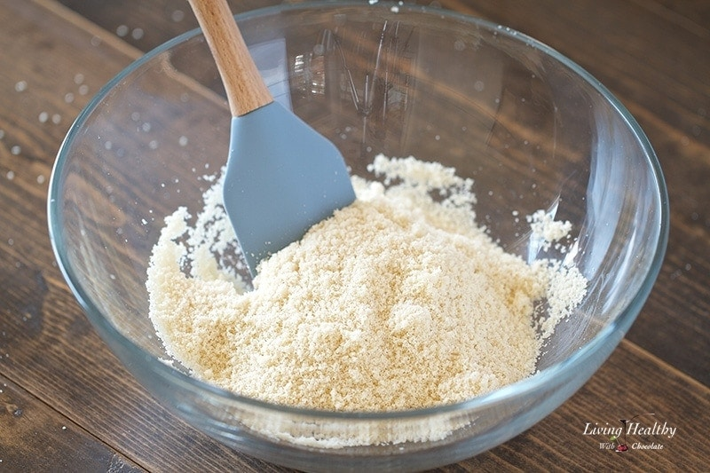 close up of a glass bowl of almond flour with spatula  sitting on wooden table