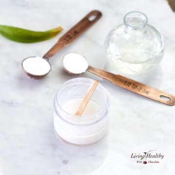 teaspoon with baking soda and oil in a jar to make natural deodorant on a marble table top
