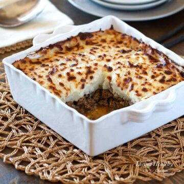 Shepherds pie in white serving dish sitting on wicker placemat with square section of pie removed