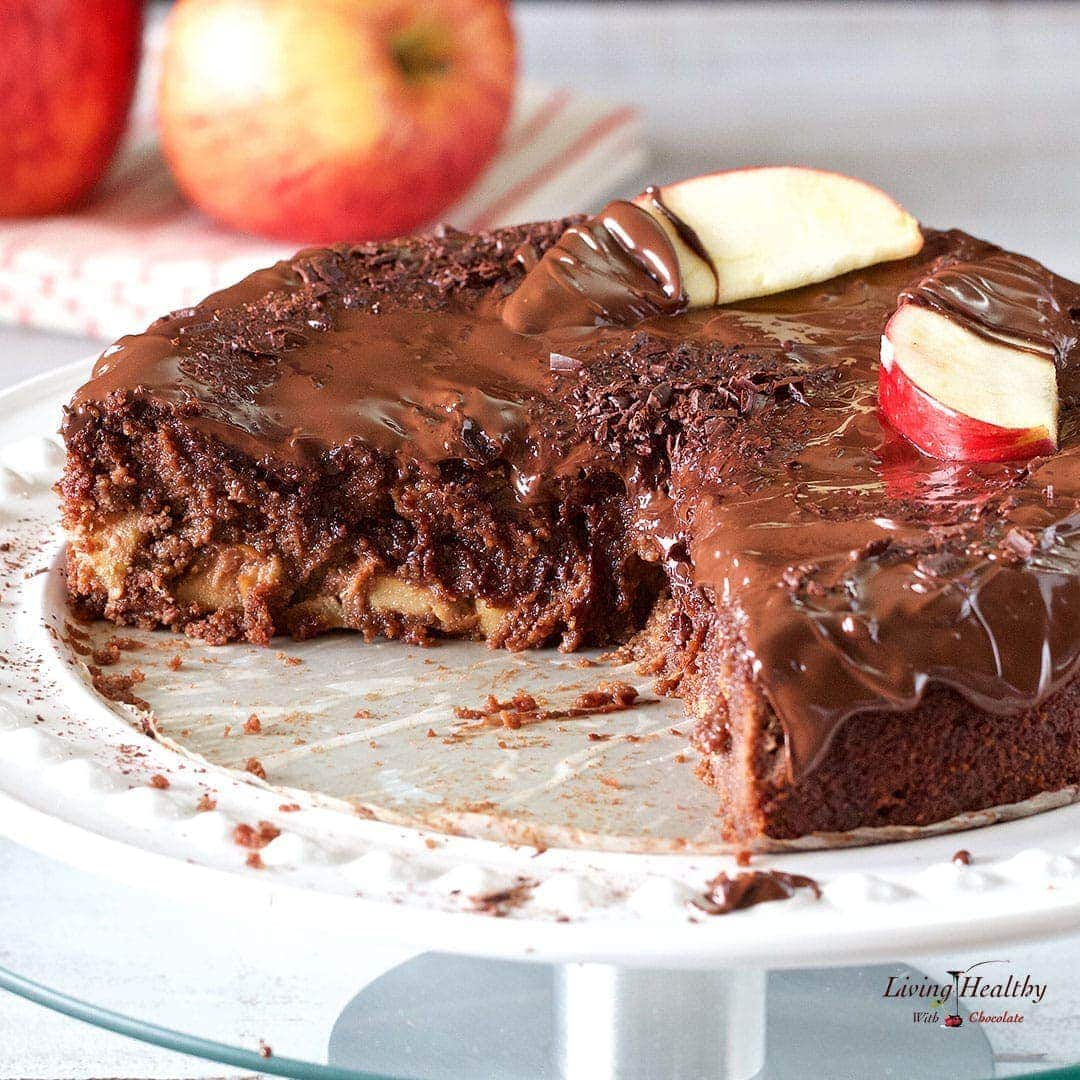 Apple chocolate cake with large slice cut out and apples on napkin in background