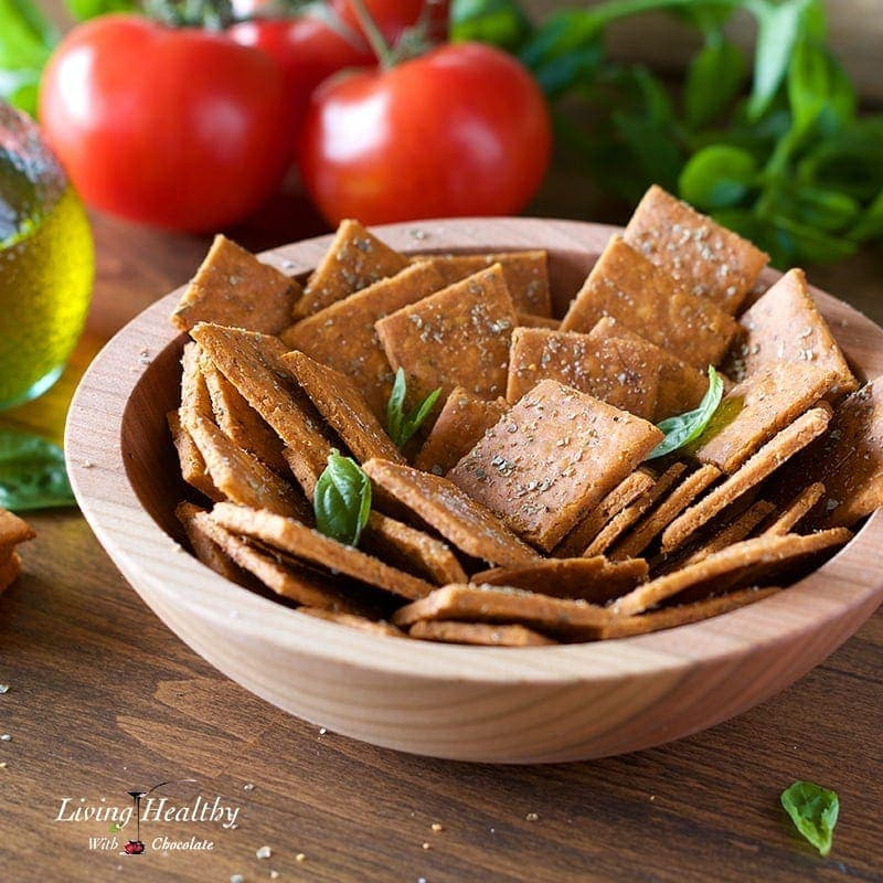 a table with cassava crackers in a wooden bowl with basil leaves, tomato and a jar of oil