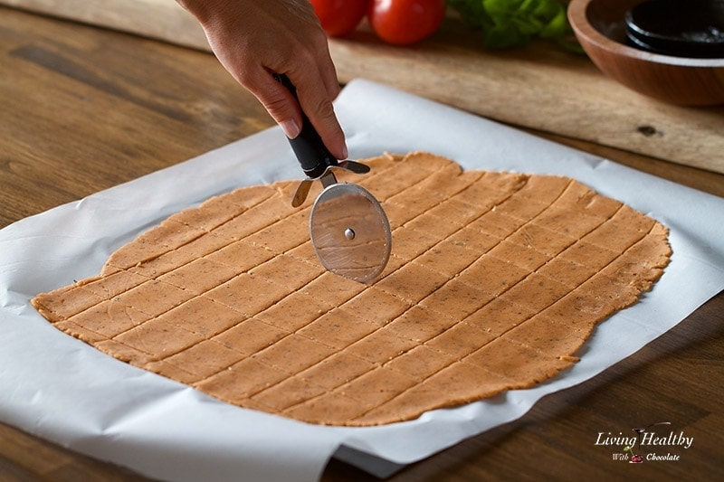 a sheet of cassava flour rolled out flat on a pan and cut into squares for crackers