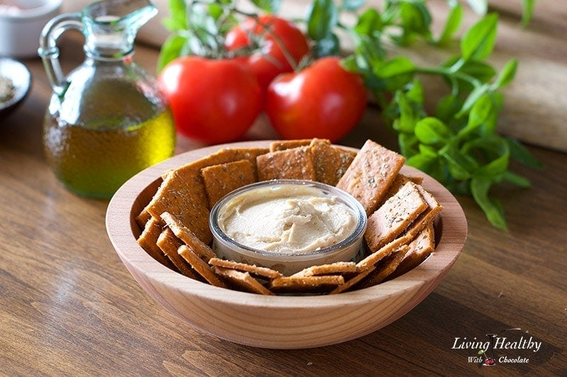 a bowl of cassava flour crackers with a small serving dish of hummus dip in the center