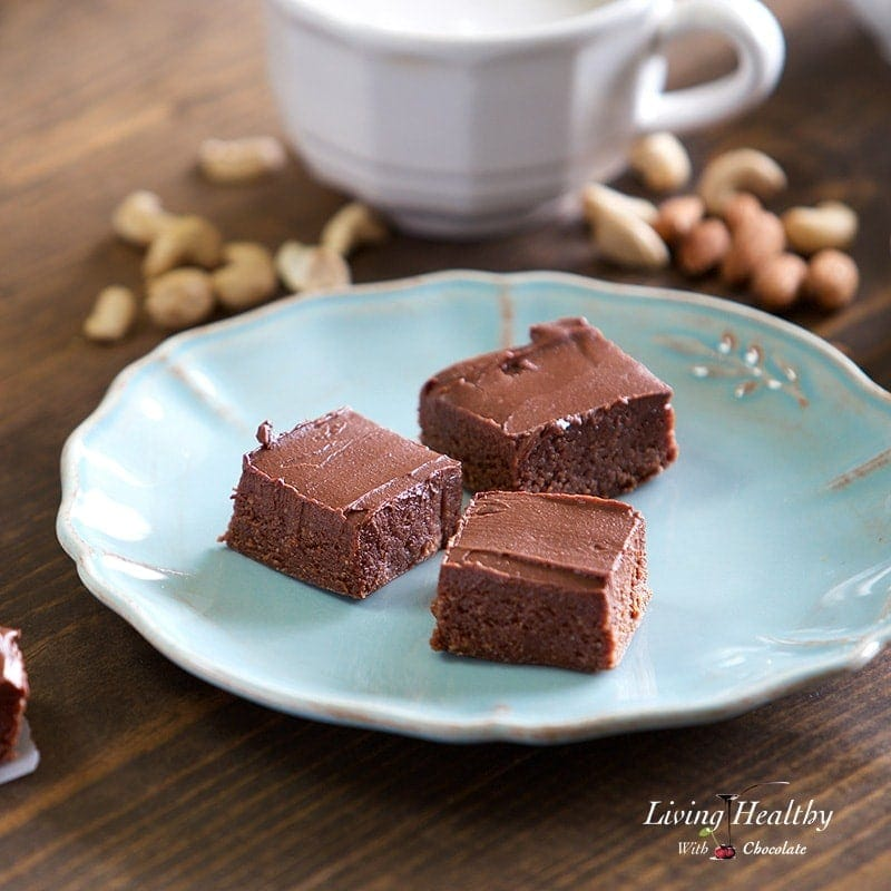 three pieces of no bake brownies on a plate with small piles of nuts and a glass of milk in the background