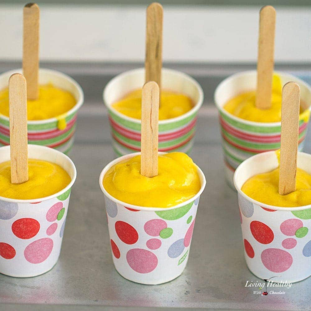Six mango smoothie popsicles in dixie cups with popsicle sticks