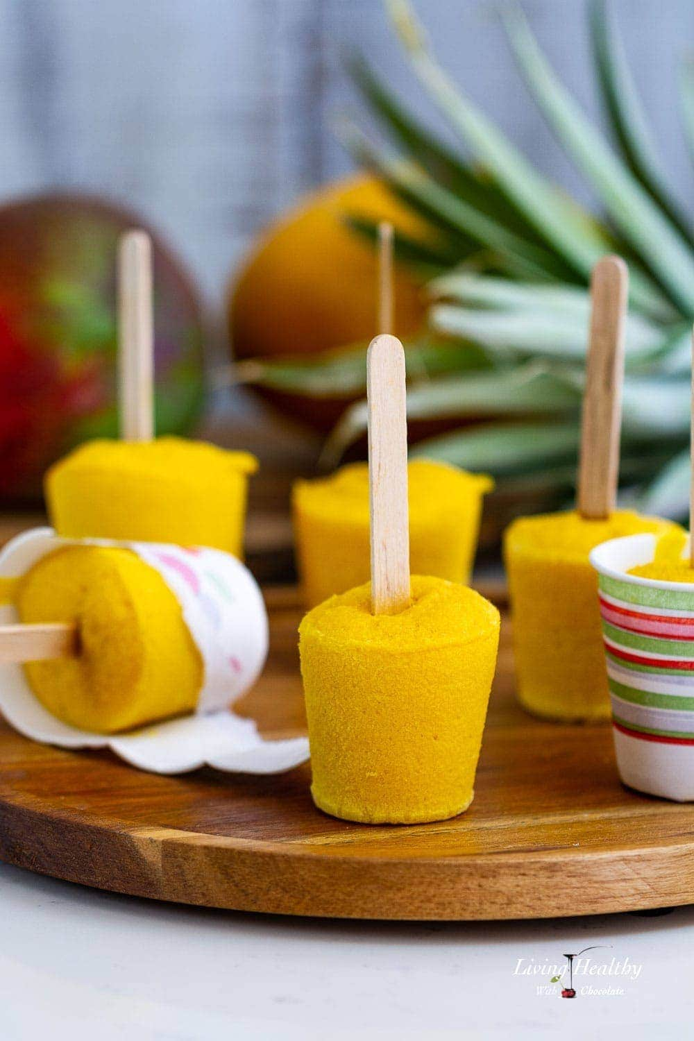 Mango smoothie popsicles on a plate with mango and pineapple behind them