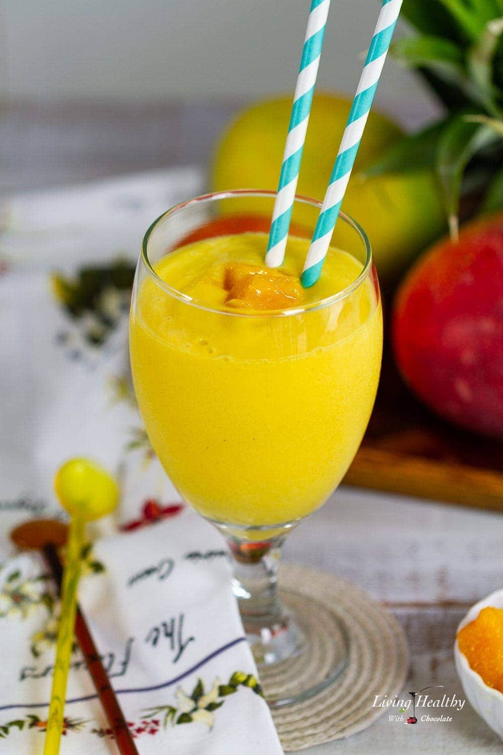 Close up of a mango smoothie in a glass with two straws