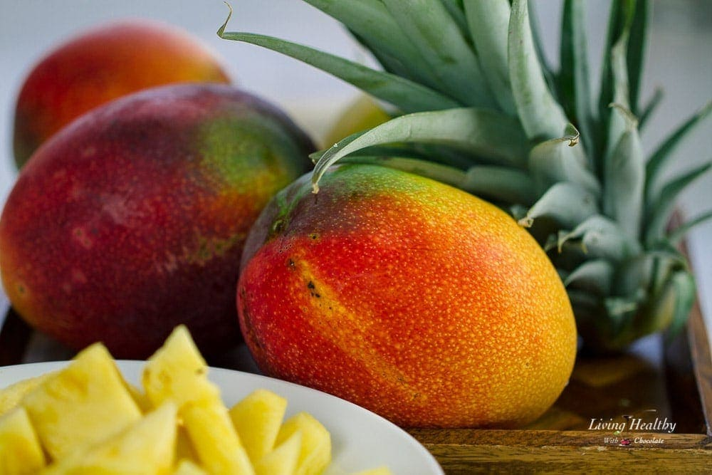 A close up of a mango and a bowl of pineapple to be used for a mango smoothie recipe