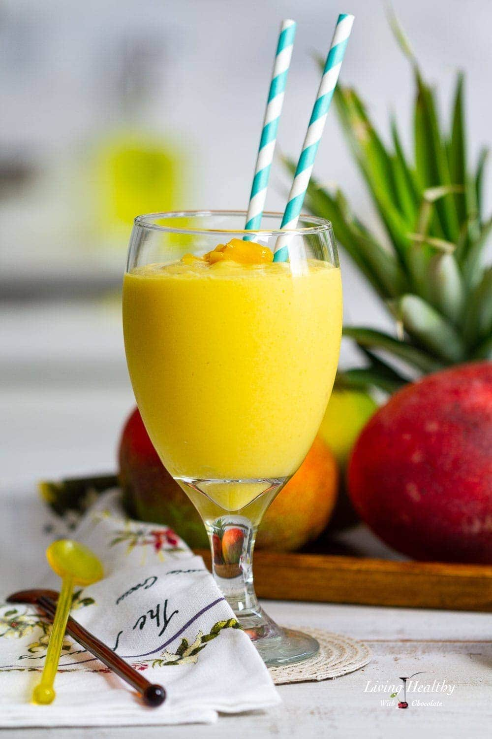 A close up of a mango smoothie with a plate of pineapple and mango behind